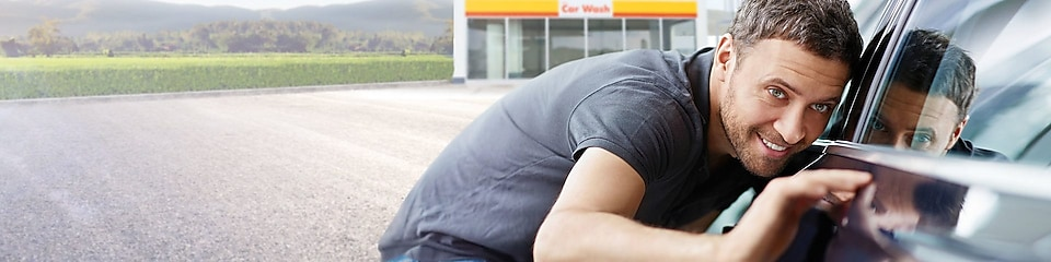 Ein junger Mann bewundert sein sauberes Auto vor einer Shell Car Wash Station